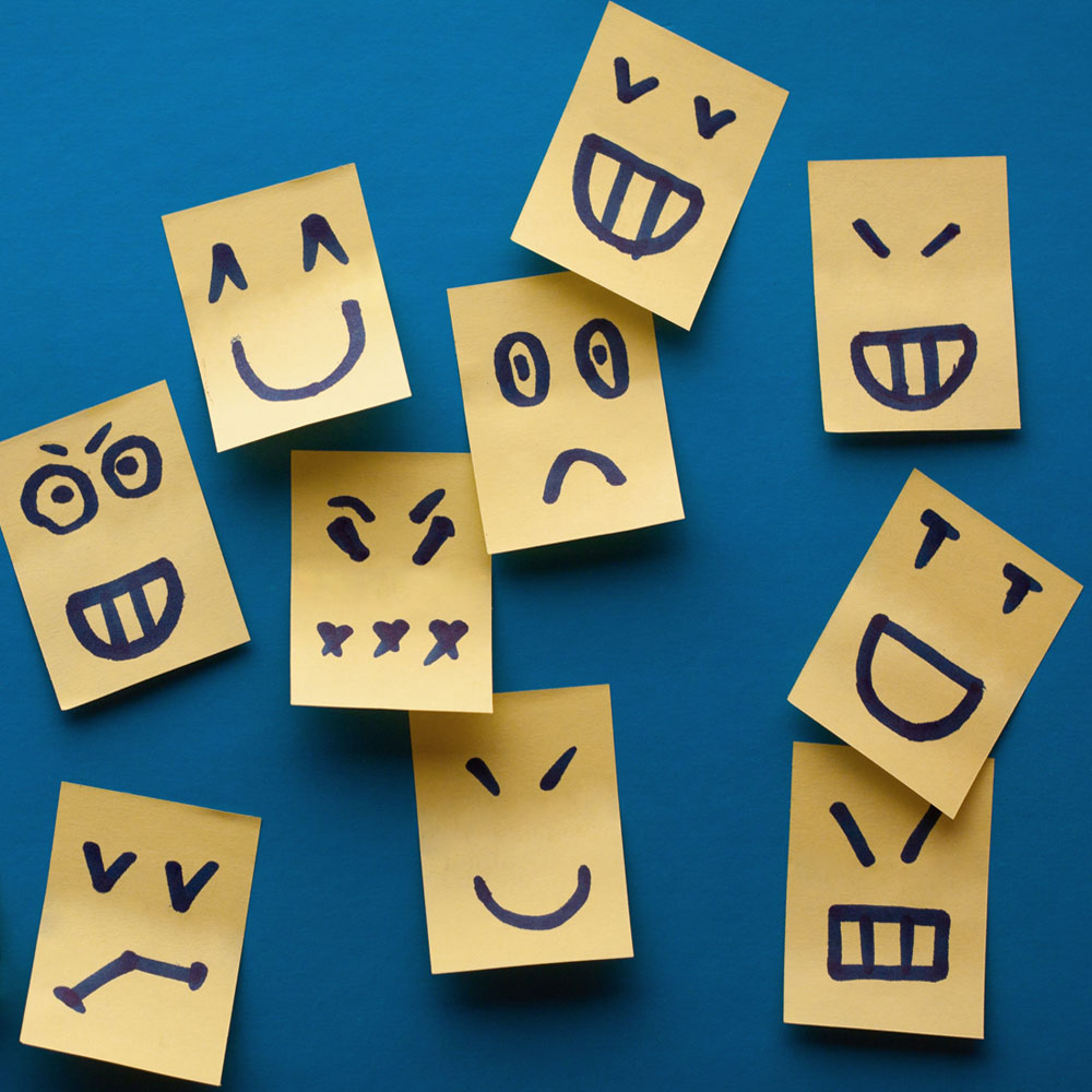 Yellow sticky notes with a variety of cartoon faces on a blue wall